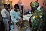 Eritrean asylum-seekers conduct a baptism ceremony for Solomon, at a side room of their makeshift church in southern Tel Aviv, Israel.
