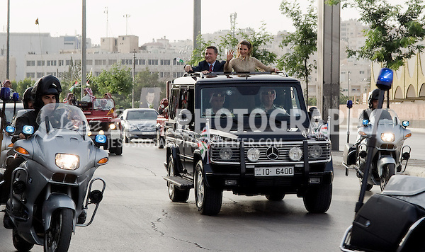 King Abdulla II and his wife Queen Rania greet the crowds from their comboy to the Stadium before the commemorative ceremonies on June 9, the King Abdullah's Ascension to the Throne Day. Amman, Jordan. Year: 2009.