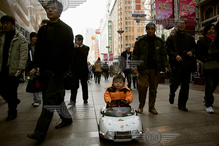 A young boy drives his toy car down Nanjing Road, followed by his grandfather on foot.