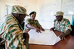 Park warden, Miriam Namushi, discussing anti-poaching strategies with her commanders, Kafue National Park, Zambia