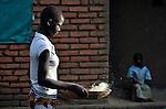 A woman winnows grain in Karonga, a town in northern Malawi.