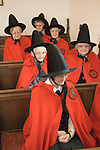 Old Ladies of Castle Rising. The Hospital of the Holy and Undivided Trinity Almshouses, Castle Rising, Norfolk, England 2007. Founders Day. The ladies wear tradiotional red cloaks and pointed black hats.Service in Chapel.