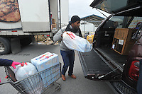 NWA Media/Michael Woods --12/17/2014-- w @NWAMICHAELW...Aaron Wilson, a volunteer from Walmart, helps load up boxes of food and toys for a local family Wednesday morning at the Salvation Army building in Springdale.  Several local volunteers helped distribute toys and food to local families for the holidays during the Salvation Army's annual event.