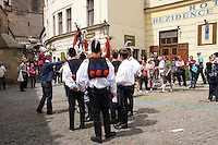 Twelve-year-old Frantisek Libosvar dressed as a girl and with a rose in his mouth leads the royal procession during Ride of the Kings as part of Navalis Celebrations on May 15, 2015 in Prague, Czech Republic. The Navalis Saint John's celebrations take place to commemorate Czech saint and Prague native, Saint John of Nepomuk, patron of all people of the water. <br /> <br /> <br /> The Ride of the Kings takes place during the spring, as a part of the Pentecost traditions . A group of young men ride through a Prague in a ceremonial procession. The ride is headed by chanters, followed by pageboys with unsheathed sabres who guard the King &ndash; a young boy with his face partially covered, holding a rose in his mouth &ndash; and the rest of the royal cavalcade. The King and pageboys are dressed in women&rsquo;s ceremonial costumes, while the other riders are dressed as men. The entourage rides on decorated horses, stopping to chant short rhymes that comment humorously on the character and conduct of spectators. The chanters receive donations for their performance, placed either in a money box or directly into the riders&rsquo; boots. The King&rsquo;s retinue returns home after a few hours of riding, and celebrates in the evening at the house of the King with a small feast, music and dancing. The practices and responsibilities of the Ride of the Kings are transmitted from generation to generation. The traditional paper decorations for the horses and the ceremonial costumes, in particular, are made by women and girls familiar with the processes, colour patterns and shapes specific to each village.
