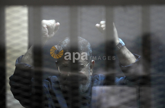 Former Egyptian president Mohamed Morsi gestures from the defendants cage as he attends his trial at the police academy on the outskirts of the capital, on June 14, 2015. Cairo criminal court resumes Sunday the trial of deposed president Mohamed Morsi and 10 others on charges of espionage and leaking classified documents related to the national security and the army. Photo by Amr Sayed
