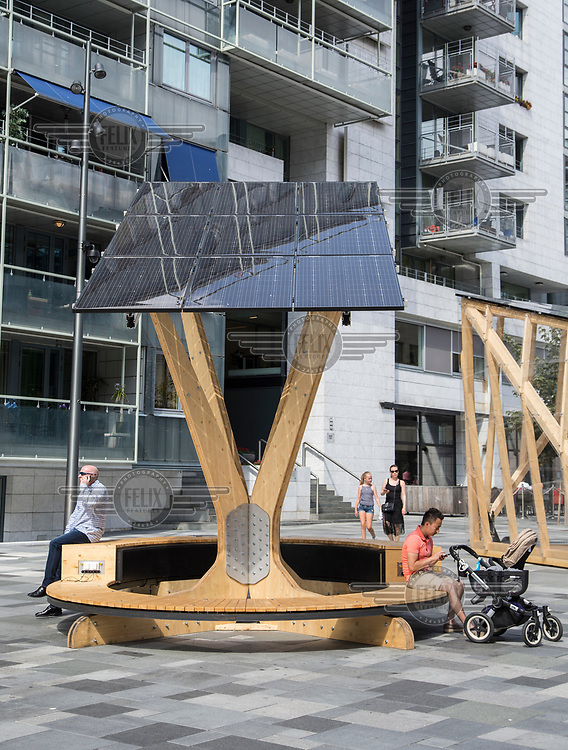 Temporary solar panels set up in public places for people to charge their mobile phones. <br />