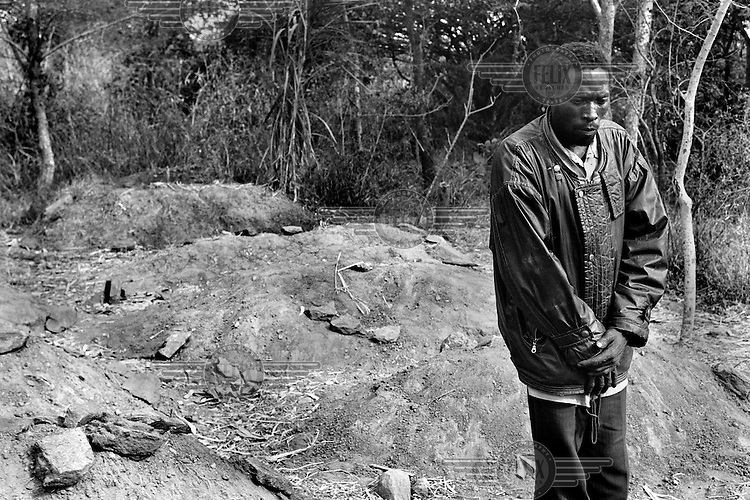 The chief of a small village outside Lilongwe, Malawi walks among fresh graves on March 9, 2001. Many adults in his village have died of AIDS, orphaning their children. More than 13 million African children have been orphaned by the AIDS pandemic. Worldwide, more than 20 million people have died since 1981.