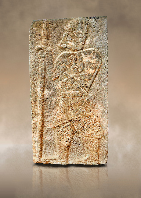 Pictures & images of the North Gate Hittite sculpture stele depicting a God with a spear. 8the century BC.  Karatepe Aslantas Open-Air Museum (Karatepe-Aslantaş Açık Hava Müzesi), Osmaniye Province, Turkey. Against art background