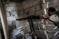 In this Tuesday, Oct. 08, 2013 photo, an opposition fighter targets his enemy position during an attack over Wadi Al-Deef military post at the frontline in Maraat Anouman in the Idlib province countryside of Syria. (AP/Photo)