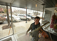 NWA Democrat-Gazette/ANDY SHUPE<br /> Window washer Hugh Swart with Fayetteville Window Washing cleans the windows at Riffraff, a store on the Fayetteville downtown square. Swart was taking advantage of the warm weather to work for clients on the square.