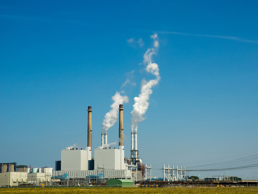 power plant against a blue sky with fumes