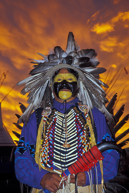 Blackfeet pow wow dancer Harold Schildt in traditional plains regalia during a spectacular sunset in Browning Montana
