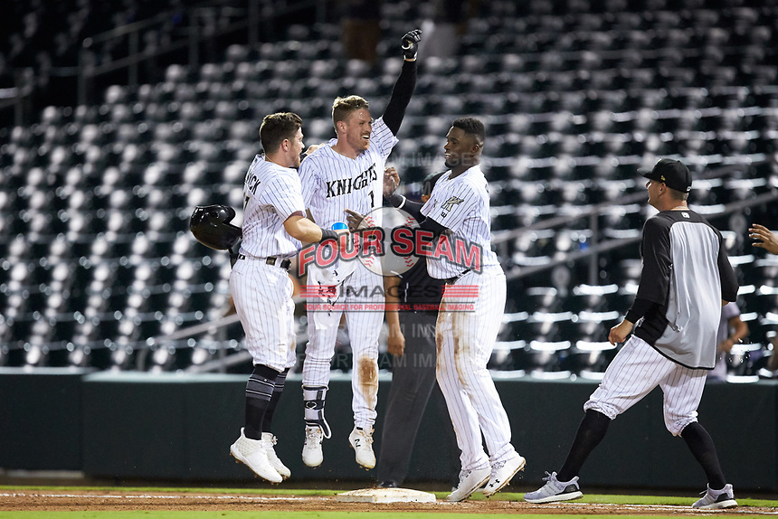 Charlie Tilson (1) of the Charlotte Knights is mobbed by his teammates after his walk-off single defeated the Scranton/Wilkes-Barre RailRiders at BB&T BallPark on August 14, 2019 in Charlotte, North Carolina. The Knights defeated the RailRiders 13-12 in ten innings. (Brian Westerholt/Four Seam Images)