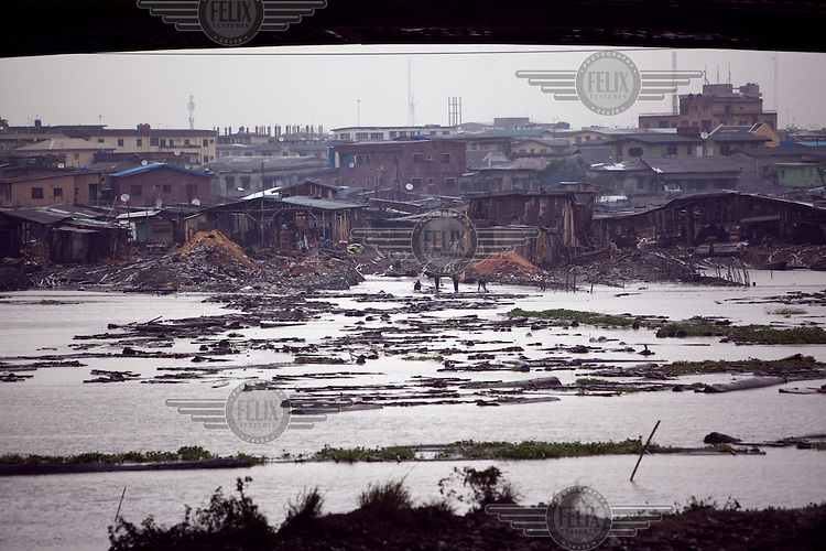 Timber floats in the waters of the Ebute Metta neighbourhood. This is the principal wood milling and timber supply area for the city. Timber is floated in rafts from north and east of Lagos and then milled and sold.