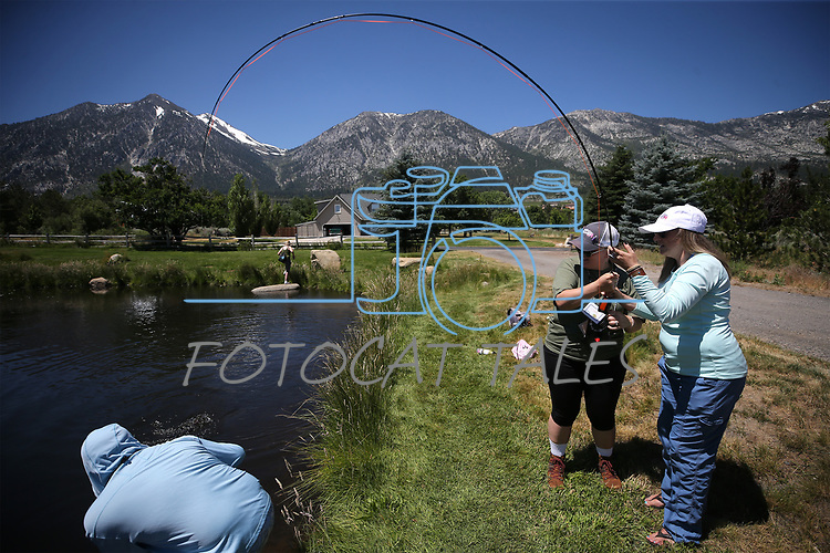 Fishing guides Jose Luna and Whitney Inmon help cancer survivor Chelle Futch with her catch during a Casting for Recovery retreat in Gardnerville, Nev., on Friday, June 30, 2017. <br /> Photo by Cathleen Allison/Nevada Photo Source