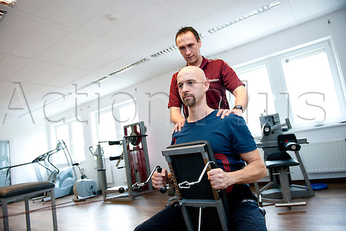 June 2012. Germany. A patient under supervision from a physical therapist is put through a series of exercises on a weight machine to aid recovery from an injury.