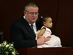 Pastor Ken Haskins gives the invocation on the Assembly floor while holding his granddaughter Arianna Haskins at the Legislative Building in Carson City, Nev. on Thursday, Feb. 7, 2013. .Photo by Cathleen Allison
