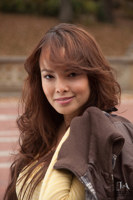 Laurence Yang with long auburn hair with a Mona Lisa Smile. Yellow blouse and sweater over her shoulder.  Laurence is an exotic beauty of French and Korean descent.