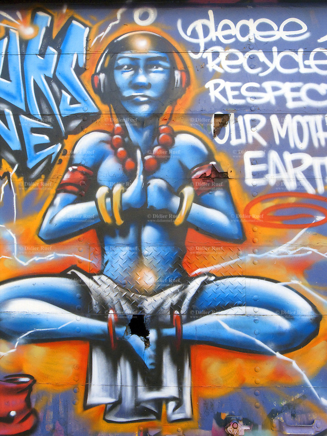 USA. New York City. On the back door of a delivery truck, a blue painted man with headsets for music is meditating as a budhist. Written words: Please recycle and respect our mother Earth.  Buddhists pursue meditation as part of the path toward Enlightenment and Nirvana. Buddhist meditation encompasses a variety of meditation techniques that aim to develop mindfulness, concentration, supramundane powers, tranquility and insight. 24.10.2011 © 2011 Didier Ruef