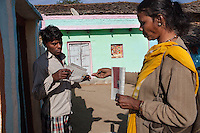 Shanti Adivasi (in yellow saree), 52, distributes this week's Khabar Lahariya newspaper to a subscriber at his home in Manikpur, Chitrakoot, Uttar Pradesh, India on 6th December 2012.  Shanti used to be a wood gatherer, working with her parents since she was 3, and later carrying up to 100 kg of wood walking 12km from the dry jungle hills to her home to repack the wood which sold for 3 rupees per kg. After learning to read and write in an 8 month welfare course, at age 32, she became a reporter, joining Khabar Lahariya newspaper since its establishment in 2002, and making about 9000 rupees per month, supporting her family of 14 as the sole breadwinner. Photo by Suzanne Lee for Marie Claire France.