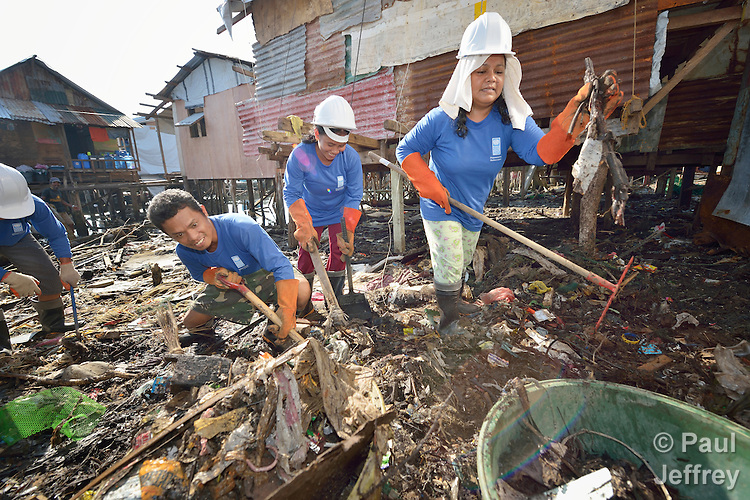 Participants in a cash for work program clean up debris in Tacloban, a city in the Philippines province of Leyte that was hit hard by Typhoon Haiyan in November 2013. The storm was known locally as Yolanda. The ACT Alliance has been active here and in affected communities throughout the region helping survivors to rebuild their homes and recover their livelihoods.