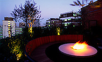 Dusk view of roof terrace with lit flambe' and view of city beyond