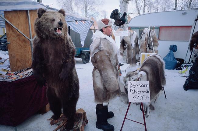 Man in a reindeer shin coat stands by a stuffed bear at the Jokkmokk Winter Market. Sweden,