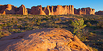 Arches National Park, UT<br /> Morning sun on petrified sand dune formations and distant Great Wall near the Courthouse Wash