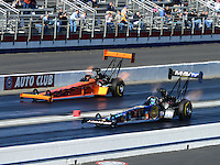 Nov. 10, 2012; Pomona, CA, USA: NHRA top fuel dragster driver Brandon Bernstein (near lane) races alongside Mike Salinas during qualifying for the Auto Club Finals at at Auto Club Raceway at Pomona. Mandatory Credit: Mark J. Rebilas-