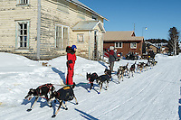 Nathan Schroeder runs down the road into the Nulato checkpoint past an old convent, turned thrift store, on Saturday afternoon March 12th during the 2016 Iditarod.  Alaska    <br /> <br /> Photo by Jeff Schultz (C) 2016  ALL RIGHTS RESERVED