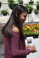 NWA Democrat-Gazette/CHARLIE KAIJO Crystal Cendejas, 18, smiles while helping a customer pick out plants to buy (not pictured), Thursday, April 12, 2018 at the Rogers High School greenhouse in Rogers.<br />