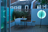 Dusk view of the tiny decked garden with the moon shaped light set into the rendered wall