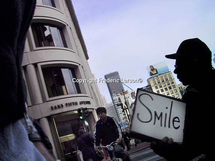 A sign of good cheer is broadcasted by a person begging for money at Powell and Post near Union Square in San Francisco, California.