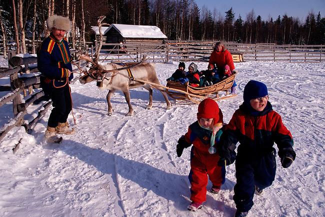 Children enjoy reindeer sled rides at a reindeer ranch. Rovaniemi. Finland