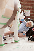 "August 9, 2012. Durham, NC.. Mary Lamb works on ""Sir Walter Cowleigh""..  Artists from all over the state have been working at Golden Belt decorating their assigned cows for the Parade of Cows, to be held this month. After the cows are displayed around the Triangle, they will be auctioned off to benefit the NC Children's Hospital."
