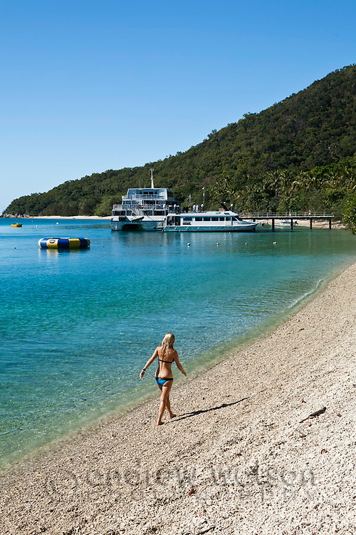 Woman walking along beach at Welcome Bay.  Fitzroy Island National Park, Cairns, Queensland, Austtralia