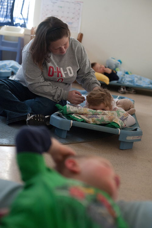 Dana Parsely comforts a child during naptime. © Ohio University / Photo by Ross Brinkerhoff
