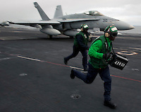 101217-N-7981E-093 PACIFIC OCEAN (Dec. 17, 2010)- Aviation Boatswain's Mate (Equipment) Airman Terrance Chase, assigned to Air Department's V-2 Division, and another Sailor run to clear the safe-shot line after displaying the weight of an F/A-18C Hornet to its pilot as the aircraft is prepared for launch on the flight deck of USS Carl Vinson (CVN 70). Carl Vinson and Carrier Air Wing (CVW) 17 are currently on a three-week composite training unit exercise (COMPTUEX) followed by a western Pacific deployment. (U.S. Navy photo by Mass Communication Specialist 2nd Class James R. Evans / RELEASED)