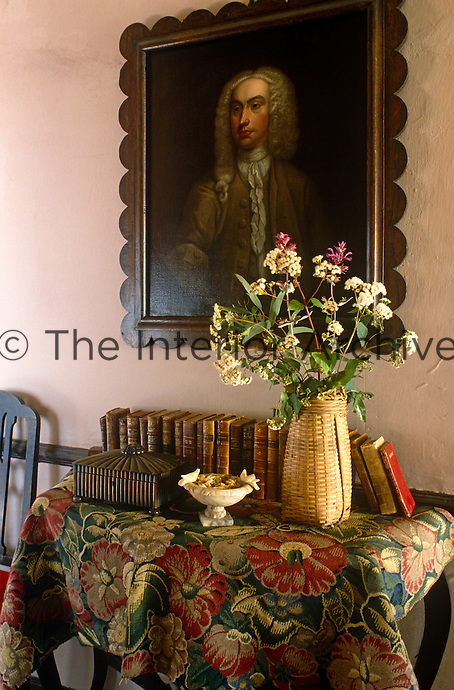 In the entrance hall an 18th-century portrait hangs above a console table displaying a collection of antiquarian books