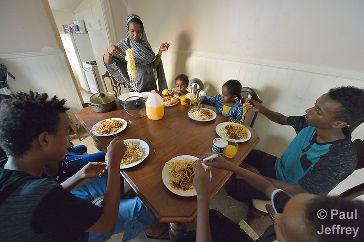 Lula Abubakar, a recently arrived refugee from Eritrea, serves spaghetti to her family their home in Lancaster, Pennsylvania. The family was resettled in the United States by Church World Service. <br /> <br /> Photo by Paul Jeffrey for Church World Service.