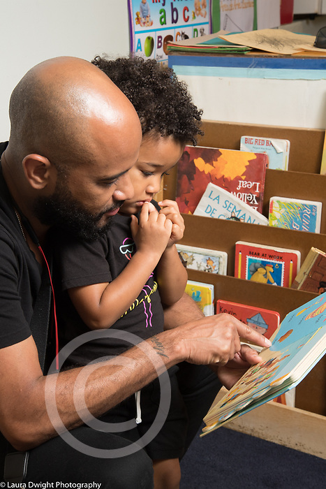 Education Preschool 2-3 year olds father reading book to son at start of day