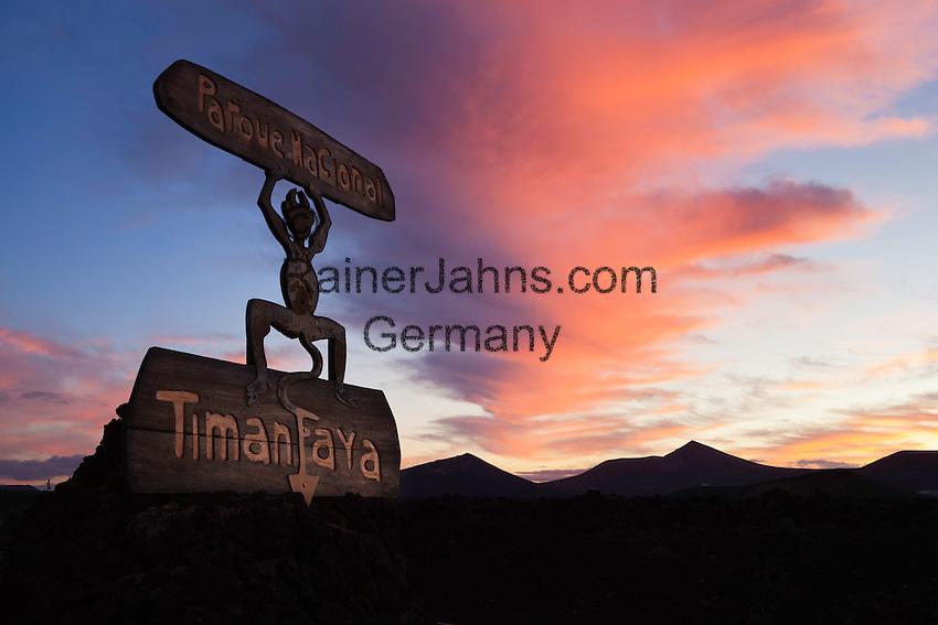 Spain, Canary Island, Lanzarote, near Yaiza: Devil symbol park entrance and volcanoes in silhouette, Parque Nacional de Timanfaya (Timanfaya National Park) at sunrise   Spanien, Kanarische Inseln, Lanzarote, bei Yaiza: Timanfaya Nationalpark (Parque Nacional de Timanfaya) - Teufelssymbol als Hinweisschild, im Hintergrund die Vulkane Montanas del Fuego (die Feuerberge) bei Sonnenaufgang