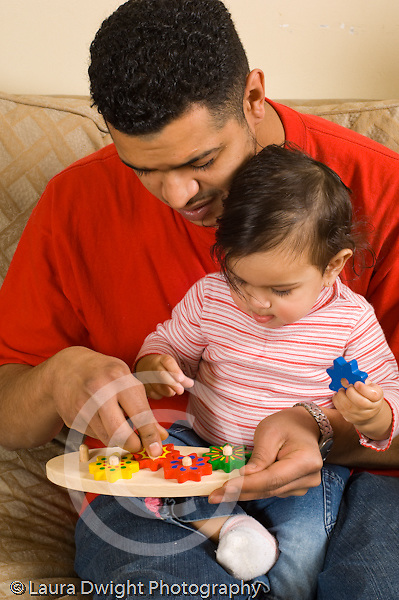 10 month old baby girl with father playing with new toy, showing her how it works demonstrating vertical