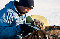 Mann slapper av i leir på en barflekk rett ved fronten av Nordmannsjøkulen på Seiland. ---- Man relaxing in camp, just beside the glacier Nordmannsjøkulen on Seiland.