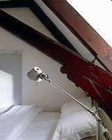 In the attic bedroom of a converted Suffolk schoolhouse a contemporary steel bedside light contrasts with one of the massive Victorian roof beams