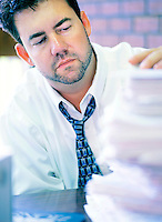 Over worked business man at his messy desk with his hands on a stack of paperwork.