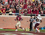 Florida State fans cheer as running back Cam Akers scores  a touchdown in front of Louisiana Monroe safety Traveion Webster in the 2nd half of an NCAA college football game in Tallahassee, Fla., Saturday, Dec. 2, 2017. Florida State defeated Louisiana Monroe  (AP Photo/Mark Wallheiser)