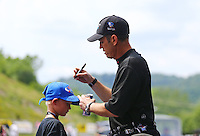 Jun 21, 2015; Bristol, TN, USA; A young fan having his hat signed by NHRA top fuel driver Larry Dixon during the Thunder Valley Nationals at Bristol Dragway. Mandatory Credit: Mark J. Rebilas-