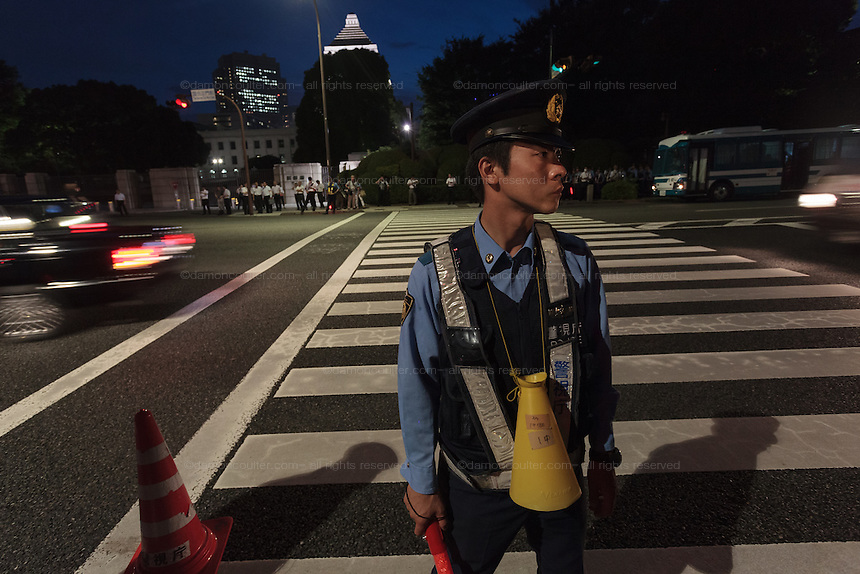 A policeman guards  a demo outside the Japanese parliament building against Prime Minister, Shinzo Abe and his reinterpretation of Article 9 of the Japanese Constitution. Nagatacho, Tokyo, Japan. Friday July 17th 2015. Around 10,000 people took part to protest a change in the law that would allow collective self-defence which was ratified in the Lower House on Thursday. Many fear this new interpretation of Japan's unique peace constitution will mean Japanese soldiers being sent to war, to aid allies such as America,