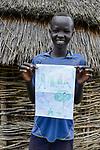 ETHIOPIA, Gambela, region Itang, Nuer village Pilual, boy Bhan 12 years old / AETHIOPIEN, Gambela, Region Itang, Dorf Pilual der Ethnie NUER, Hof von Herr Mun Kunen und Frau Neelam , sie sind vor dem Buergerkrieg aus dem Suedudan gefluechtet, Sohn Bhan 12 Jahre mit einem selbstgemaltem Bild